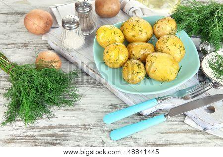 Batatas cozidas no cilindro na placa de madeira perto de guardanapo na mesa de madeira