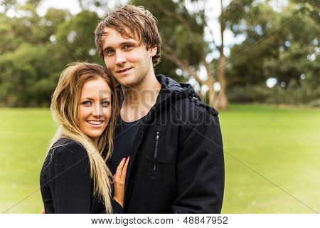 Close up portrait of a young smiling attractive couple, caucasian, in a beautiful outdoor park garden