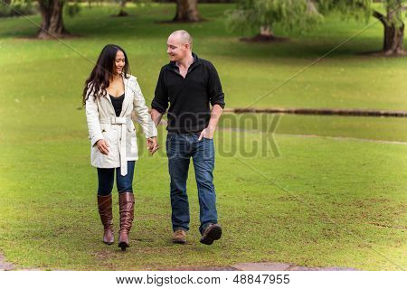 romantic happy young couple holding hands walking in a beautiful park