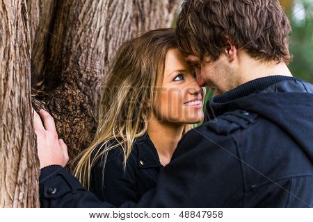 Close up portrait of a romantic young couple standing next to a tree