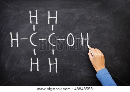 Alcohol ethanol on blackboard in chemistry class. Ethanol alcohol chemical molecule structure on chalkboard. Science teacher or chemistry student drawing chemical formula on blackboard in class.