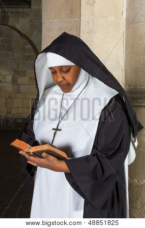 Mature nun reading the bible in a medieval church