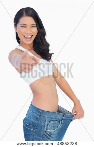 Victorious woman holding her too big pants and pointing out at camera on white background
