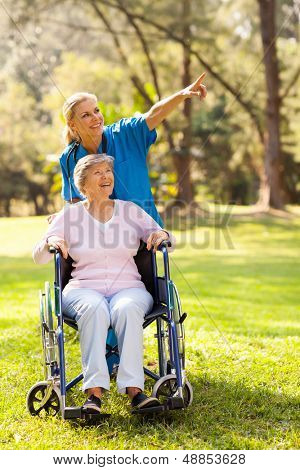 friendly nurse taking disabled elderly patient for a walk