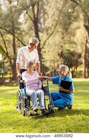 pretty female doctor greeting recovering senior patient in wheelchair outdoors