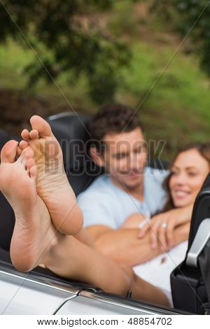Happy couple cuddling in the backseat with focus on foot in a convertible