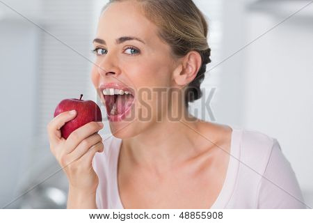 Woman in her kitchen munching apple