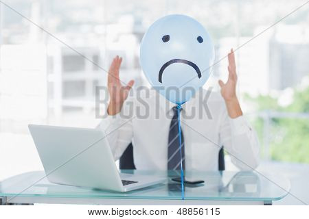Blue balloon with sad face hiding angry businessmans face in bright office