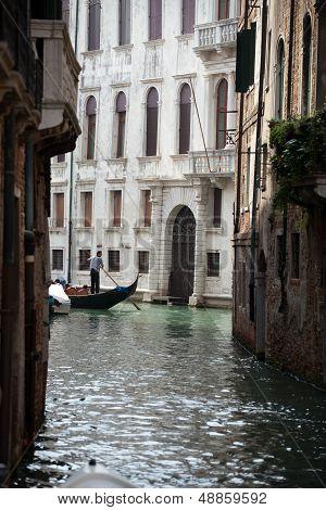 Narrow canal with gondolas in Venice Italy