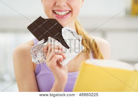 Closeup On Teenager Girl With Book And Chocolate Bar