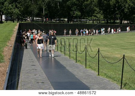 WASHINGTON, DC - JULY 29: Tourists walk along the Vietnam Memorial on July 29, 2013 in Washington. The memorial honors U.S. service members who fought in the Vietnam War.