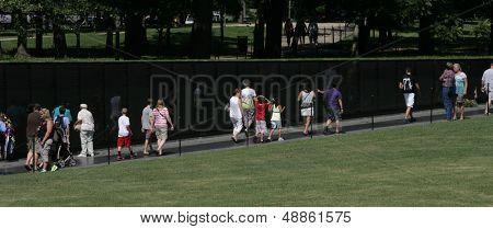 WASHINGTON, DC - JULY 29: Tourists walk along the Vietnam Memorial on July 29, 2013 in Washington. The memorial honors U.S. service members who fought in the Vietnam War.