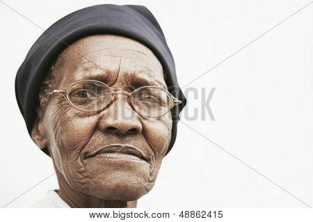 Closeup portrait of elderly woman wearing glasses over white background