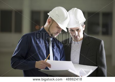 Young male architects going through file folder in warehouse