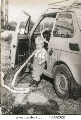 Vintage photo of little boy vacuuming a car, eighties