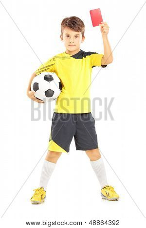 Full length portrait of a kid in sportswear holding soccer ball and giving red card isolated on white background