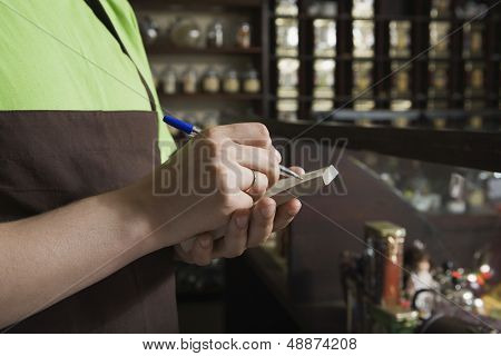 Cropped image of saleswoman writing order in book at tea shop