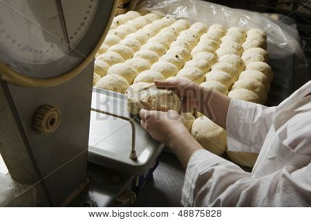 Male baker weighing ball of bread dough in bakery