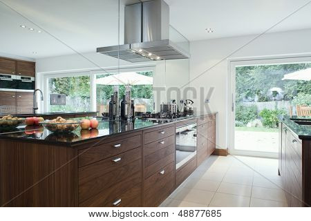 Fruits and bottles on countertop with wooden drawers in modern kitchen