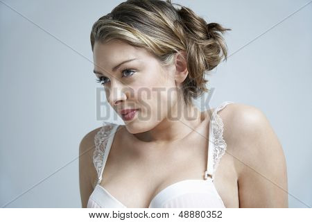 Beautiful sensuous woman in bra isolated over colored background