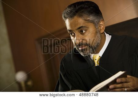 Middle age male judge with book looking away in court room