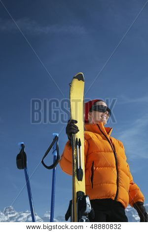 Low angle view of happy woman in winter jacket holding ski against blue sky