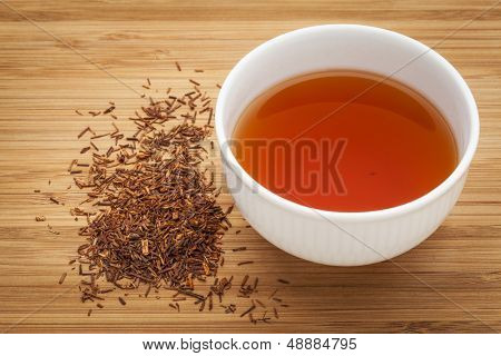 rooibos red tea  -  a white cup of a drink and loose leaves on bamboo wood background, tea made from the South African red bush, naturally caffeine free