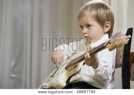 Side view of a cute little boy playing guitar