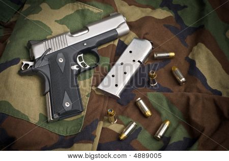 45 Firearm Pistol Clip And Hand Gun Ammunition On Camouflage