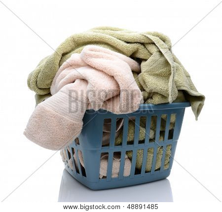 Laundry basket full of towels. The plastic basket is isolated on a white background.
