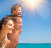 stock photo of sun-tanned  - Happy Young Family with Little Child Having Fun at the Beach - JPG