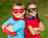 stock photo of arm muscle  - Pretty mixed race girl and Caucasian boy pretending to be superhero - JPG