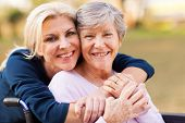 stock photo of cheers  - cheerful middle aged woman embracing disabled senior mother outdoors - JPG