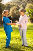 caring female nurse greeting recovering senior patient outdoors
