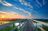 stock photo of morning sunrise  - charming wooden bridge for bicycles over river at sunrise - JPG