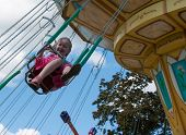 picture of carousel horse  - girl riding on a carousel in the park on summer day - JPG