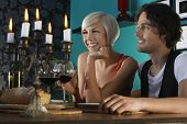 Smiling young couple with wineglasses enjoying dinner party