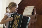 stock photo of accordion  - Side view of a young girl playing the accordion - JPG
