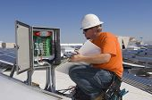stock photo of kneeling  - Electrical engineer holding book while analyzing electricity box at solar power plant - JPG