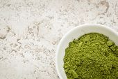 image of moringa oleifera  - moringa leaf powder in a small bowl against a ceramic tile background with a copy space - JPG