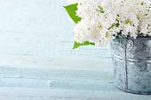 foto of bouquet  - Bouquet of white lilac spring flowers in a wooden blue vase on light shabby chic background - JPG