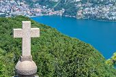 picture of salvatore  - Cross on a church rooftop on the top of Mount San Salvatore with mountain panorama landscape view in Lugano Lake Como district at Italian and Swiss border - JPG