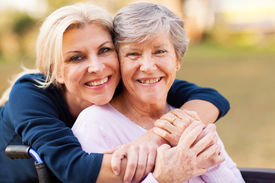 foto of retirement age  - cheerful middle aged woman embracing disabled senior mother outdoors - JPG