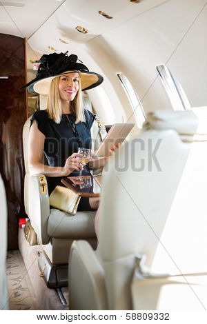 Portrait of rich confident woman with digital tablet and drink glass sitting in private jet