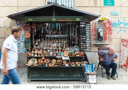 SARAJEVO, BOSNIA AND HERZEGOVINA - AUGUST 11, 2012: Salesman with traditional souvenirs on old town Bascarsija, popular place for tourists to buy local craftwork.