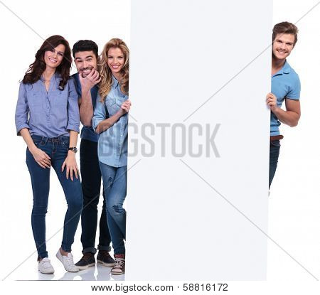 group of casual people fooling around and presenting a blank board on white background