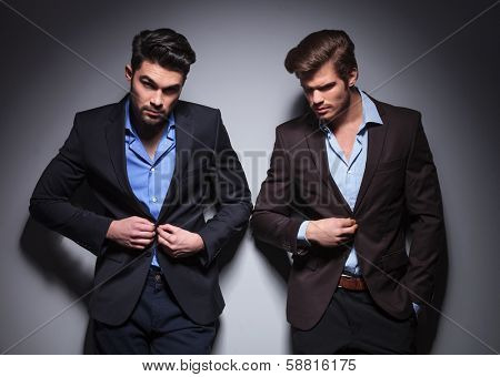 serious men posing in studio, one buttoning his coat, one looking away