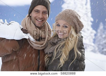 Happy young loving couple going ice skating in snowfall, smiling happy, holding ice skates.