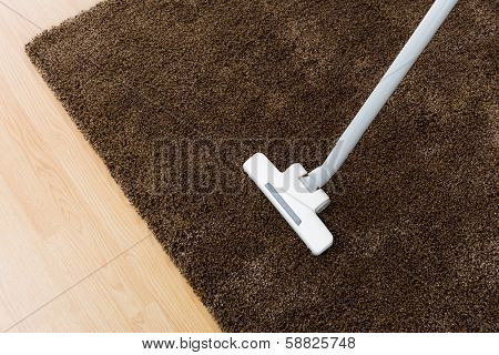 Head of modern vacuum cleaner on carpet