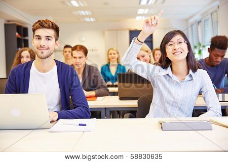 Asian student raising her hand in a university classroom
